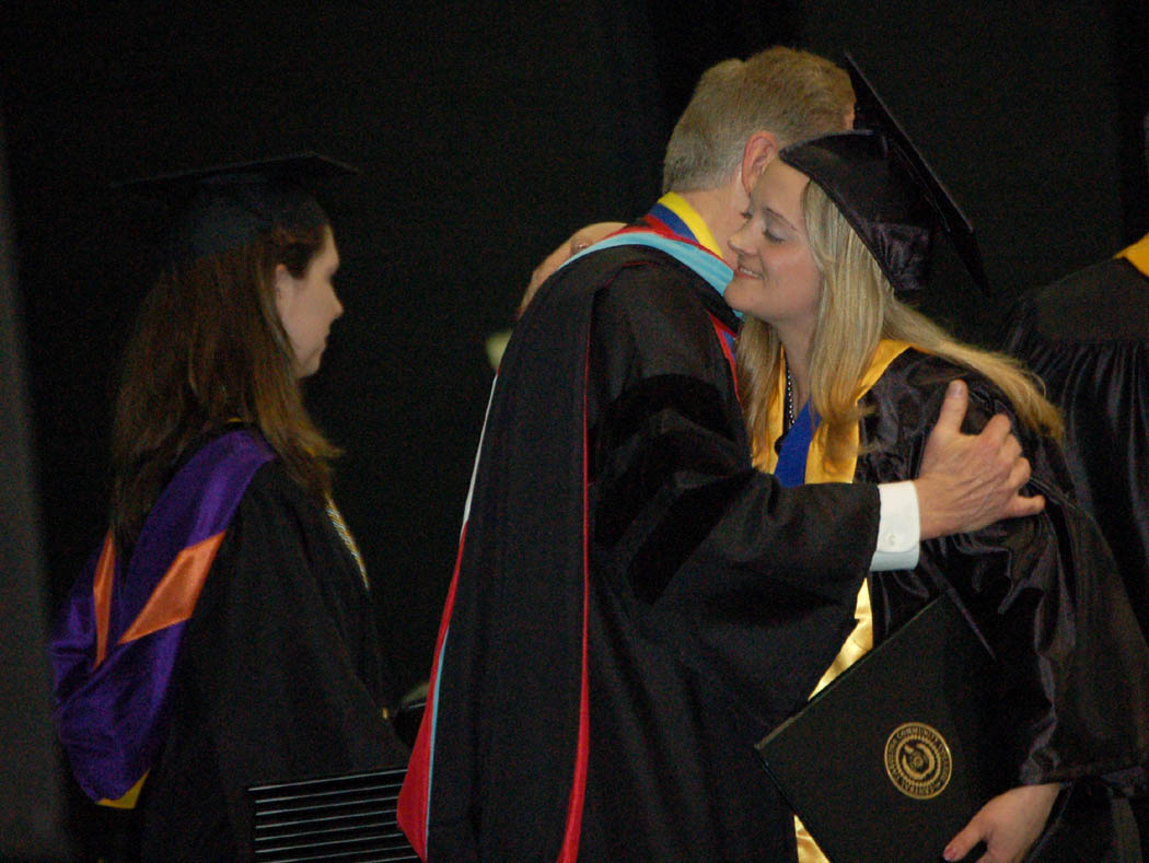 Click to enlarge,  Jennifer Marano (right), of Sanford, receives a congratulatory hug from Central Carolina Community College President Matt Garrett after she received her AAS in Paralegal Technology at the college's graduation Friday at the Dennis A. Wicker Civic Center. Marano, who graduated from college 19 years after she graduated high school, was the student speaker for the degree program graduation. Biology instructor Jessica Brown (left), the college's 2008 Instructor of the Year, assists with the awarding of degrees.