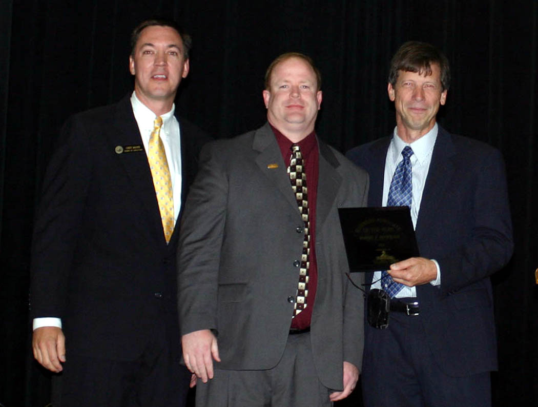 Click to enlarge,  Robert Patterson (center), senior vice president of First Bank, in Sanford, was honored as the Small Business Advocate of the Year at the 23rd Annual Central Carolina Small Business Banquet, held May 8 at the Dennis A. Wicker Civic Center, in Sanford. Presenting the award were Chet Mann (left), chairman of the Sanford Area Chamber of Commerce, and David Nestor (right), vice chairman of the Chamber. The Chamber and the Small Business Center of Central Carolina Community College put on the event. Charlie Daniels, country and pop music legend, was the guest of honor for the banquet and received a Lifetime Achievement Award for his musical career. Robert and Peggy Smith, owners of Smith's Coffee and Premium Water Co., in Sanford, were honored as Small Business Persons of the Year.