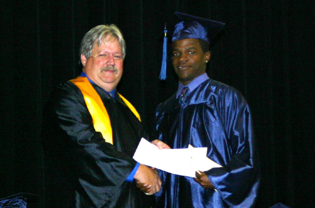 Click to enlarge,  Tim McNeill (left), vice chairman of the Central Carolina Community College Board of Trustees, presents the W.B. Wicker Memorial Scholarship to Shawn Thornton, of Sanford, who received his GED diploma Thursday at the college's Adult High School and GED programs graduation in the Dennis A. Wicker Civic Center.