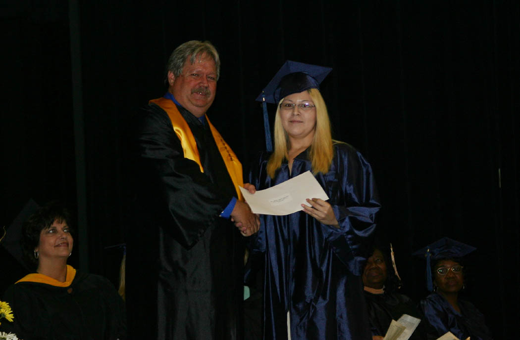Click to enlarge,  Tim McNeill (left), vice chairman of the Central Carolina Community College Board of Trustees, presents Maria Gonzalez-Chavez, of Lee County, with a $600 CCCC Foundation Directors' Scholarship during the college's Adult High School and GED programs graduation Thursday at the Dennis A. Wicker Civic Center. Gonzalez-Chavez received her GED diploma during the exercises.