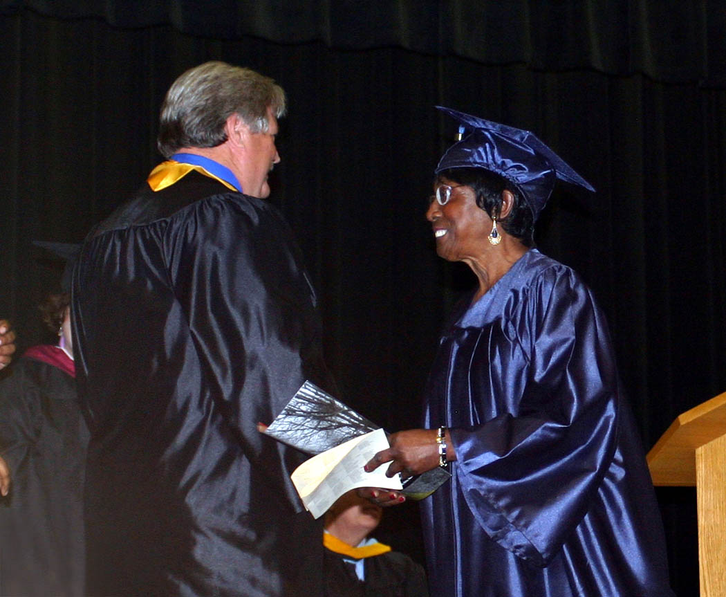 Click to enlarge,  Tim McNeill (left), vice chairman of the Central Carolina Community College Board of Trustees, congratulates Willie Mae Stokes, of Angier, at the college's Adult High School and GED programs' commencement ceremonies Thursday at the Dennis A. Wicker Civic Center. Stokes, 69, received her GED diploma.