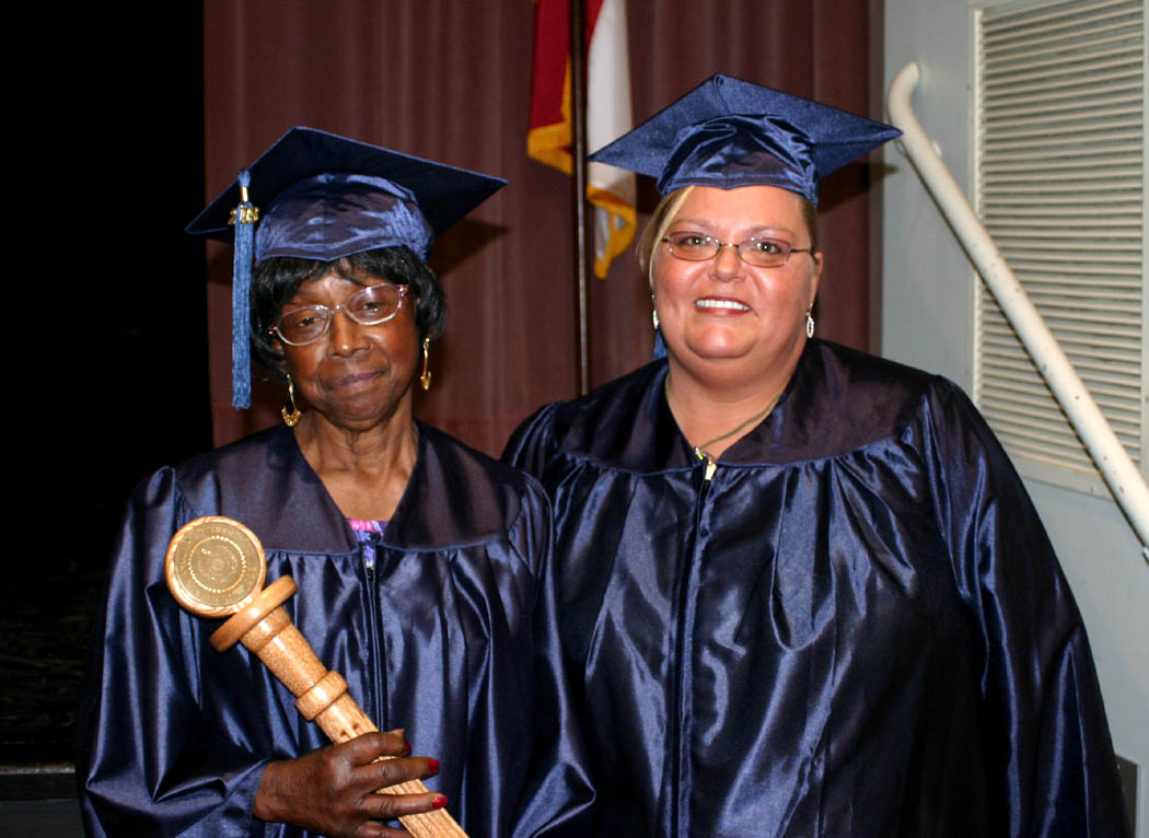 Click to enlarge,  Willie Mae Stokes (left), of Angier, had the honor of carrying the mace and leading the processional and recessional Thursday at Central Carolina Community College's Adult High School and GED programs' graduation, held in the Dennis A. Wicker Civic Center in Sanford. Cristie Mitchell (right), of Lillington, was the Harnett County speaker for the event. Both completed their studies for a GED diploma during the spring semester.