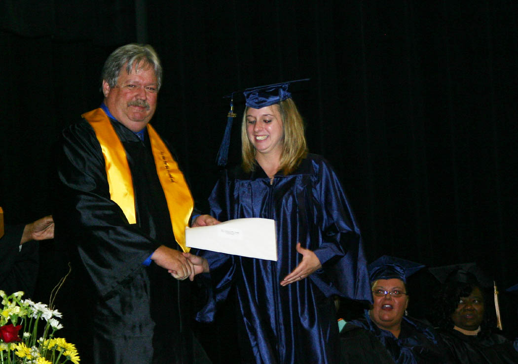 Click to enlarge,  Tim McNeill (left), vice chairman of the Central Carolina Community College Board of Trustees, presents Tanya Smith, of Goldston, with a $600 CCCC Foundation Directors' Scholarship during the college's Adult High School and GED programs' graduation Thursday at the Dennis A. Wicker Civic Center. Smith received her high school diploma. She was also one of three student speakers for the event.