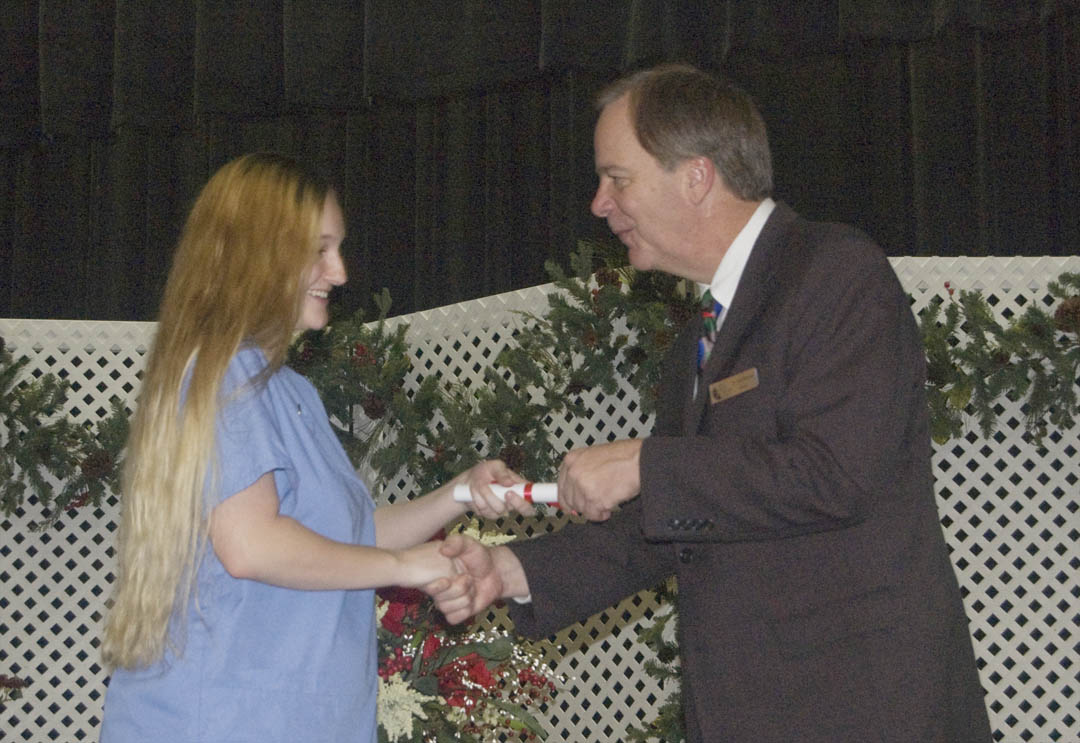 Click to enlarge,  Fall graduates of the Central Carolina Community College-Lee County Continuing Education Department's Medical Programs crossed the stage at the Dennis A. Wicker Civic Center Dec. 17 to receive their certificates. More than 100 of the graduating students took part in the ceremony. Among them was Amanda Corum (left), of Harnett County, who received her Nursing Assistant-I certificate from college President Bud Marchant (right).