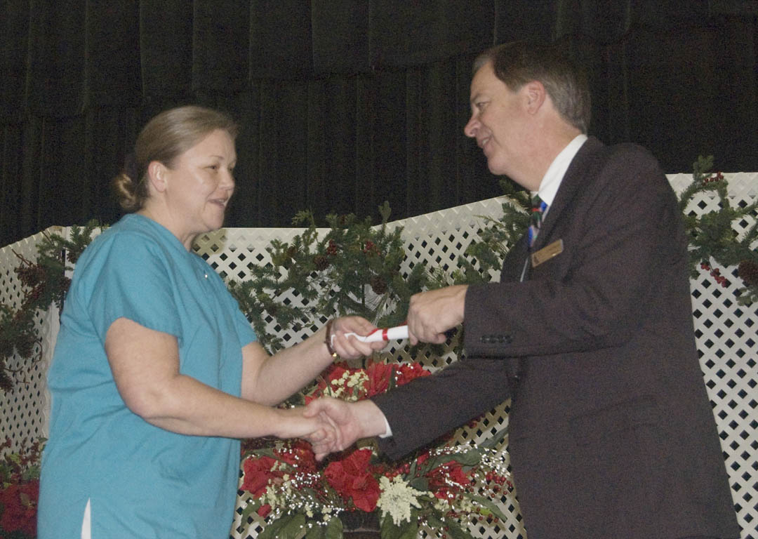 Click to enlarge,  Fall graduates of the Central Carolina Community College-Lee County Continuing Education Department's Medical Programs crossed the stage at the Dennis A. Wicker Civic Center Dec. 17 to receive their certificates. More than 100 of the graduating students took part in the ceremony. Among them was Rhonda H. Venable (left), of Moore County, who received her Nursing Assistant-I certificate from college President Bud Marchant (right).
