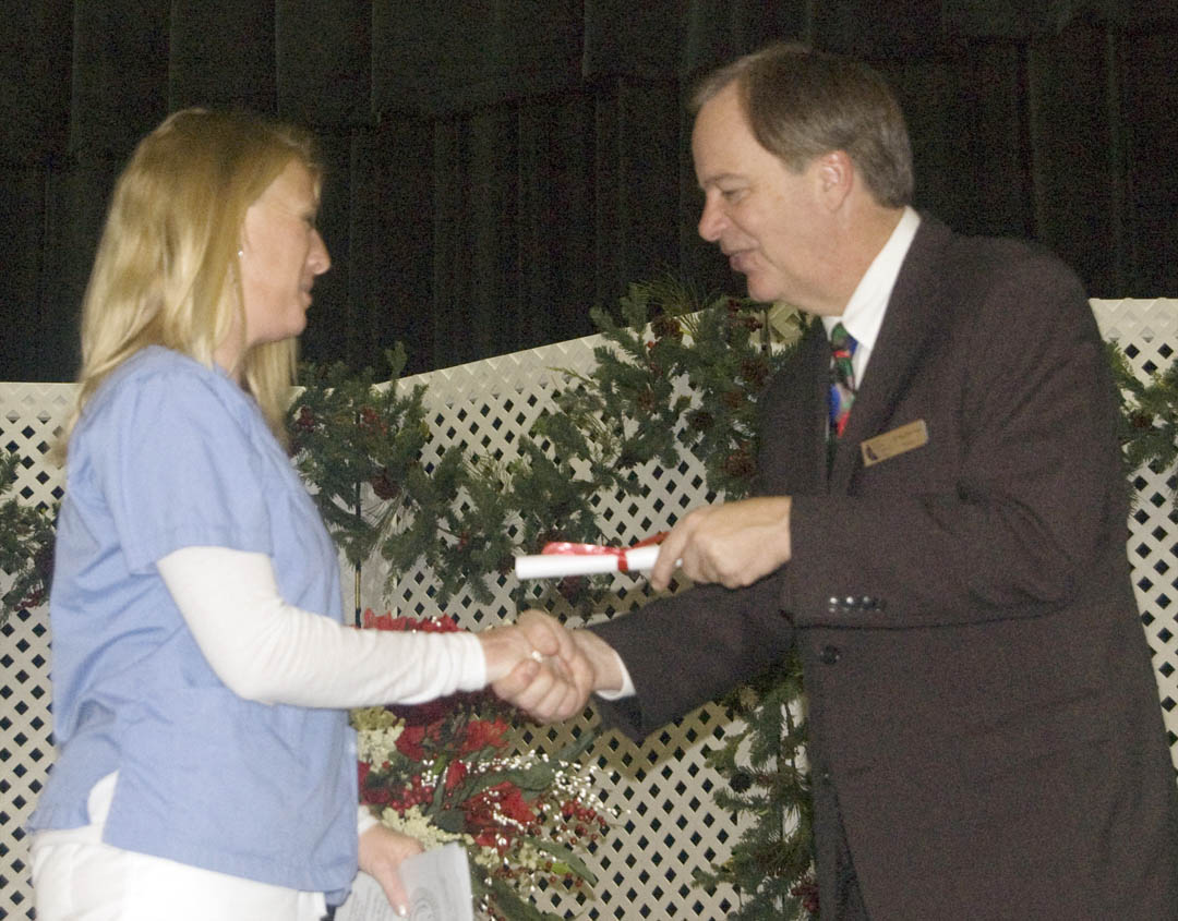 Click to enlarge,  Fall graduates of the Central Carolina Community College-Lee County Continuing Education Department's Medical Programs crossed the stage at the Dennis A. Wicker Civic Center Dec. 17 to receive their certificates. More than 100 of the graduating students took part in the ceremony. Among them was Amy Clark Hayes (left), of Chatham County, who received her Nursing Assistant-I certificate from college President Bud Marchant (right).