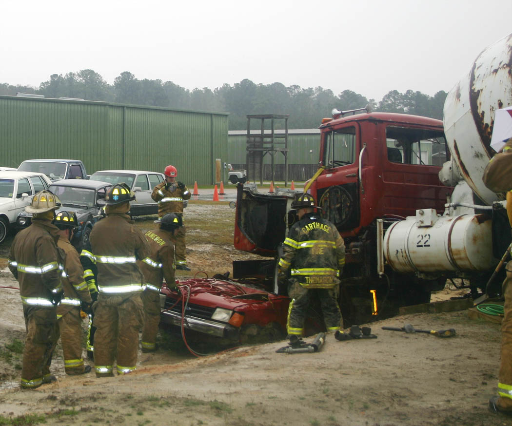 Click to enlarge,  Firefighters and rescue squad members from departments in three states and North Carolina practice running airbag hoses under a concrete mixer truck to raise it off the passenger car curshed beneath it. The training was part of the Big Rig Rescue scenario held recently at Central Carolina Community College's Emergency Services Training Center, in Sanford. Firefighters and rescue squad members came from Virginia, South Carolina and Indiana, as well as nine North Carolina towns and cities, to learn how to safely work with this type of accident. The ESTC not only provides critical training for emergency services personnel, but also boosts the local economy as those coming from out of the area stay at motels, eat at restaurants, and make purchases locally while here.