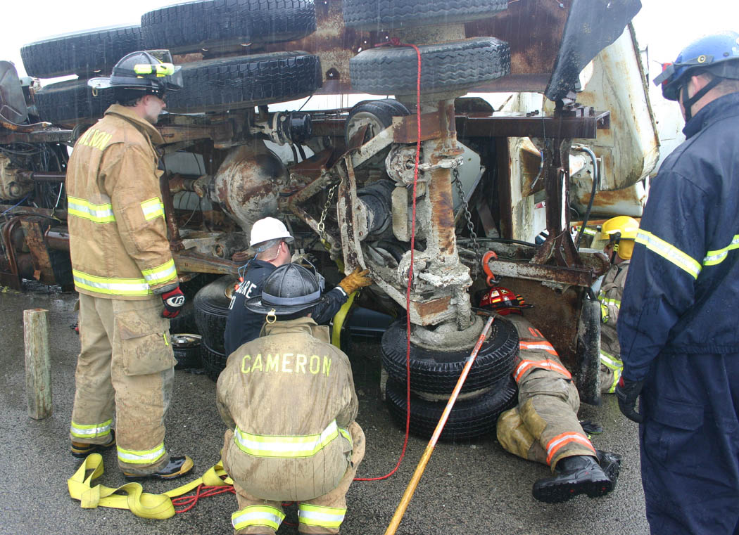Click to enlarge,  Firefighters from both local and out-of-state fire departments learn how to fasten a strap around an overturned concrete mixer truck in order to stabilize it and raise it to release the car beneath it. The training was part of the Big Rig Rescue scenario held recently at Central Carolina Community College's Emergency Services Training Center, in Sanford. Firefighters and rescue squad members came from Virginia, South Carolina and Indiana, as well as nine North Carolina towns and cities, to learn how to safely work with this type of accident. The ESTC not only provides critical training for emergency services personnel, but also boosts the local economy as those coming from out of the area stay at motels, eat at restaurants, and make purchases locally while here.
