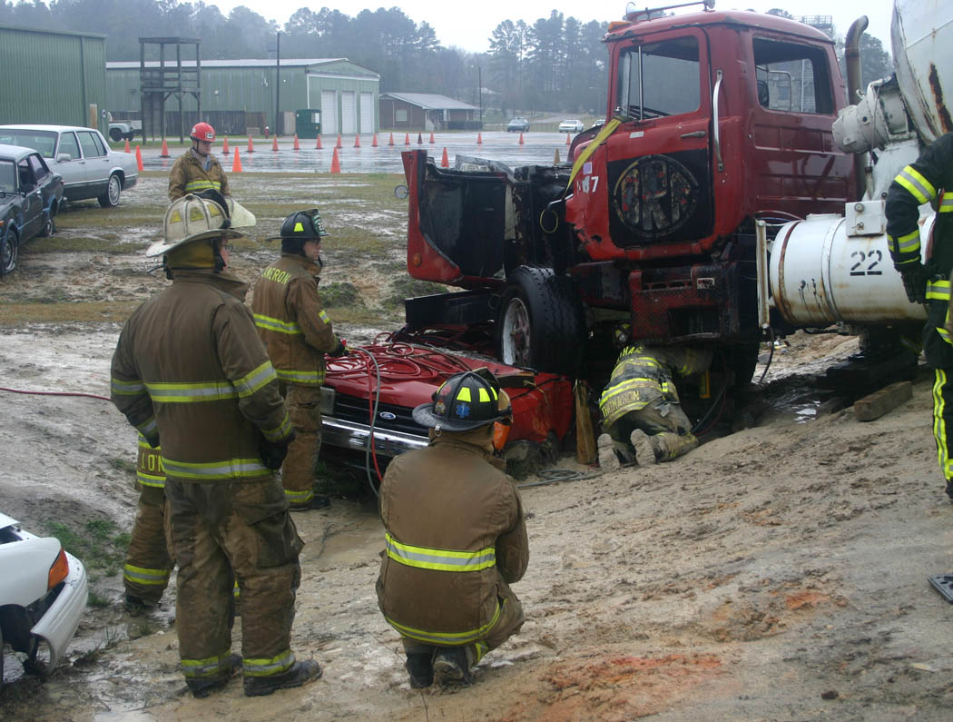 Click to enlarge,  Firefighter Chad Thomason (under truck), of the Carthage Fire Department, places a stabilizing strut under a concrete mixer truck that is crushing a passenger car. The experience was part of the Big Rig Rescue scenario held recently at Central Carolina Community College's Emergency Services Training Center, in Sanford. Firefighters and rescue squad members came from Virginia, South Carolina and Indiana, as well as nine North Carolina towns and cities, to learn how to safely work with this type of accident. The ESTC not only provides critical training for emergency services personnel, but also boosts the local economy as those coming from out of the area stay at motels, eat at restaurants, and make purchases locally while here.