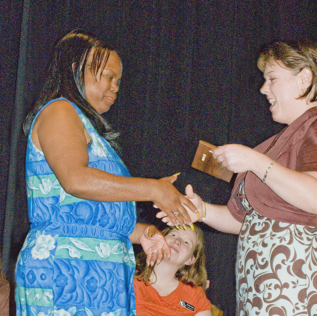 Click to enlarge,  Central Carolina Community College student Angela Wallace (left), of Sanford, was among students honored at the college's 14th annual Academic Excellence Awards program May 6 at the Dennis A. Wicker Civic Center. Wallace received the Academic Excellence in Early Childhood Associate Award from Ginger Harris-Pike, chair of the college's Early Childhood Education Department, as math instructor Christine Taylor, (center, seated) watches. The college and departments honored 66 graduating students for excelling academically, being outstanding students, serving as Ambassadors, being selected for Who's Who Among Students in America's Junior Colleges, and other achievements.