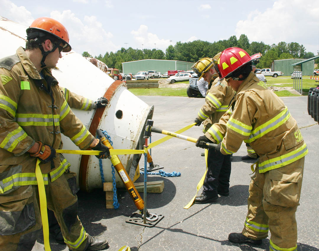Click to enlarge,  Firefighters Jon Slusar (left) of the Abingdon (Md.) Fire Department, and Francis Malta (back), of the Frederick (Md.) Fire Department, pull on a strap to hold a spike being hammered by Tim Sapp, of the Pooler (Ga.) Fire Department during a scenario at the 'Big Lift U' heavy load lifting training event June 13-14 at Central Carolina Community College's Emergency Services Training Center in Sanford. The spike fastens a strut to the road surface so the strut can help stabilize a concrete drum that has fallen on a car in the simulated accident. Once stabilized, airbags are used to raise the drum off the car. In a real accident, the firefighters would then be able to rescue people in the car. During 'Big Lift U', these firefighters and 74 others from eight states and Germany learned how to safely and effectively respond in eight different accident scenarios involving smaller vehicles with large, heavy vehicles, such as tractor-trailers, buses, concrete trucks, and a train. For more information on ESTC emergency training programs, call (919) 776-5601.
