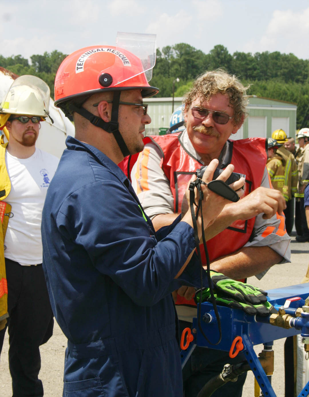 Click to enlarge,  Irakli West (center), captain of the Haar Fire Department in Bavaria, Germany, speaks with Kevin Cieciorka, of Pittsboro, owner of Chatham County Alignment & Towing and an instructor, at the 'Big Lift U' training June 13-14 at Central Carolina Community College's Emergency Services Training Center. The event trained 77 firefighters from eight states and one foreign country to safely and effectively respond to accidents involving smaller vehicles with large, heavy vehicles, such as tractor-trailers, buses, concrete trucks, and a train. West came to learn more about extrication in these types of accidents. He also runs Germany's largest online firefighters' magazine, Feuerwehr im Netz, and has posted photographs and commentary there about his Big Lift experience (see  fwnetz.de . For more information on ESTC emergency training programs, call (919) 776-5601.