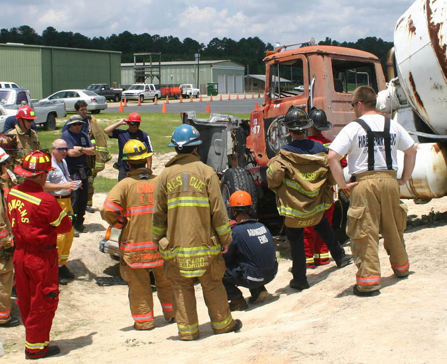 Click to enlarge,  Firefighters from several states assess a multiple-vehicle collision scenario with a tractor-trailer on a passenger car in a ditch before acting to lift the larger vehicle from the smaller. The training scenario took place during the 'Big Lift U' heavy load accident training June 13-14 at Central Carolina Community College's Emergency Services Training Center in Sanford. Instructor Billy Leach (gray shirt, left), a certified wreckmaster and developer of Big Rig Rescue training, provides pointers on how to stabilize and raise the tractor-trailer to reach accident victims in a real collision of this type. Leach organized the 'Big Lift' event, which attracted 77 firefighters from eight states, as well as Germany.  During the two-day hands-on training, firefighters worked hands-on with eight different accident scenarios involving smaller vehicles with tractor-trailers, bus, and train. For more information on ESTC emergency training programs, call (919) 776-5601.