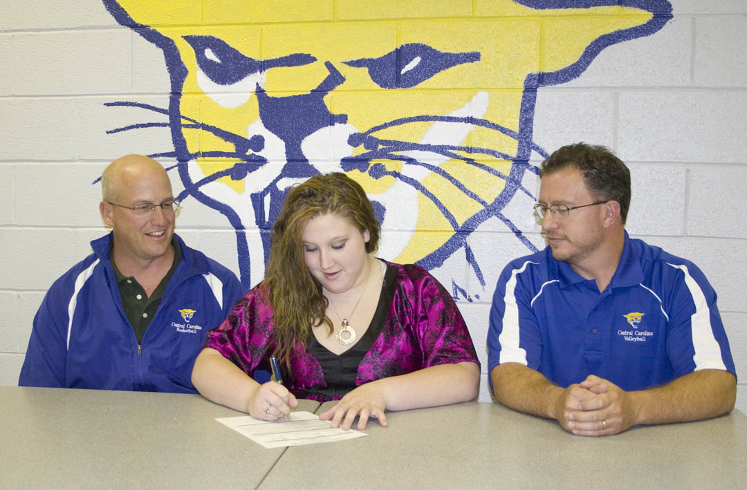 Click to enlarge,  Jordan West (center), of Spring Lake, Harnett County, signs her letter of intent to play volleyball for Central Carolina Community College's Cougars as Athletic Director Mike Neal (left) and coach Bill Carter watch. She is an outside/middle hitter, but Carter sees her as a team leader because she is very well rounded and brings strengths in hitting, setting, and passing.