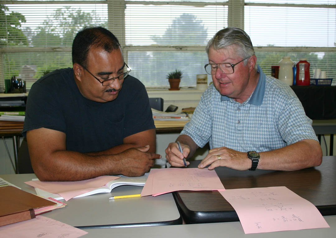 Click to enlarge,  Volunteers provide a spark for learning to students in Central Carolina Community College's Adult Basic Education programs at the Jonesboro Center, in Sanford. They work one-on-one with students to help them grasp the concepts they need to gain their high school or GED diplomas. Volunteer John Altenburger, of Carolina Trace, helps student Alberto Rivera, of Sanford, with his math studies. Altenburger, a General Motors product engineer who retired in 1992, has tutored more than 1,000 students at the Center since he started 13 years ago.