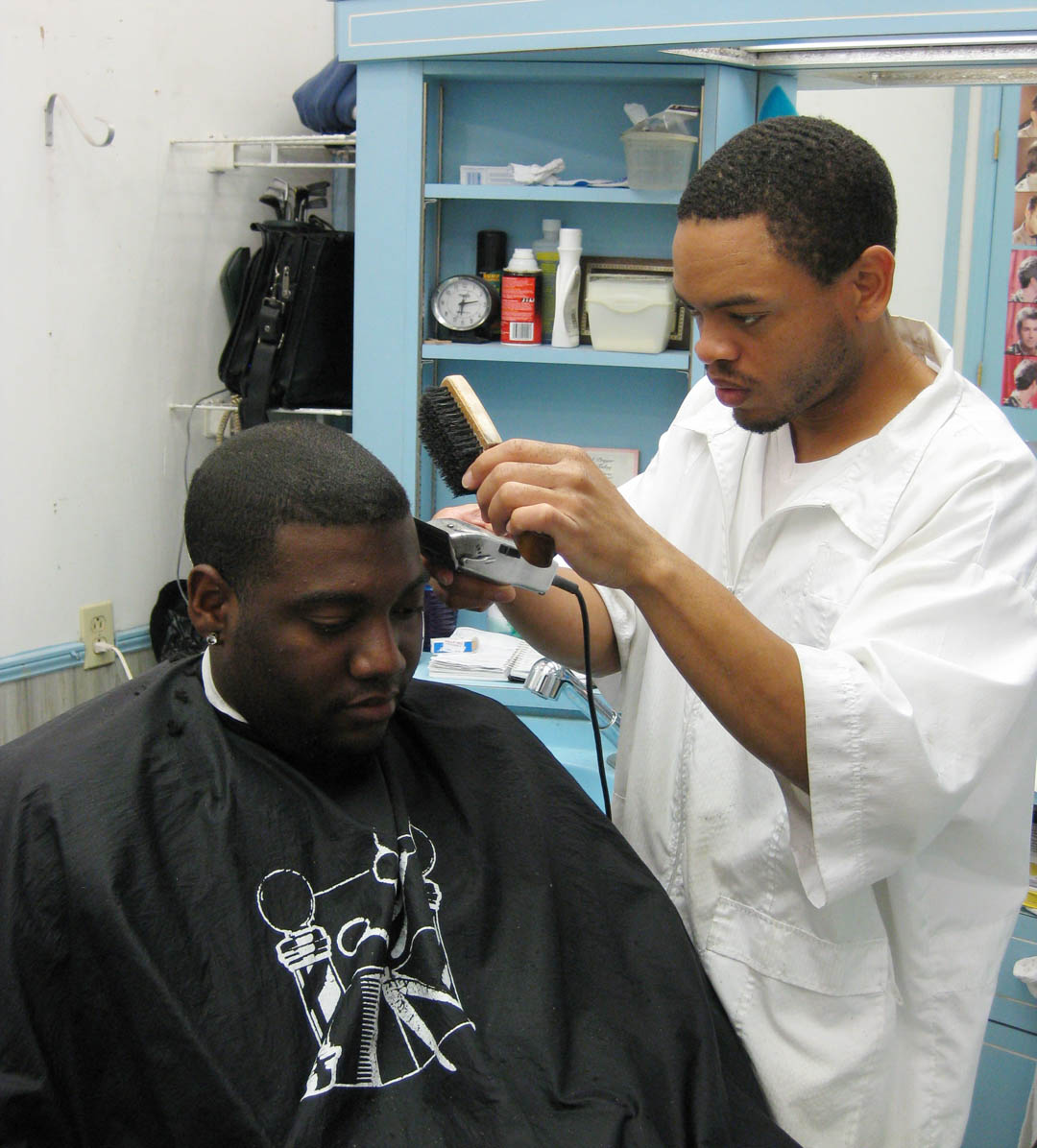 Click to enlarge,  Barber Eric Brown (right) trims the hair of Jonathan Brome, one of therncustomers at Brown's new barbershop, Carolina Barbershop, in ChapelrnHill. Brown, a 2001 graduate of Sanford Barber College, and his wife,rnTru, both of Carrboro, learned how to establish their small businessrnwith the help of Central Carolina Community College's Chatham SmallrnBusiness Center, located at the college's Pittsboro Campus.