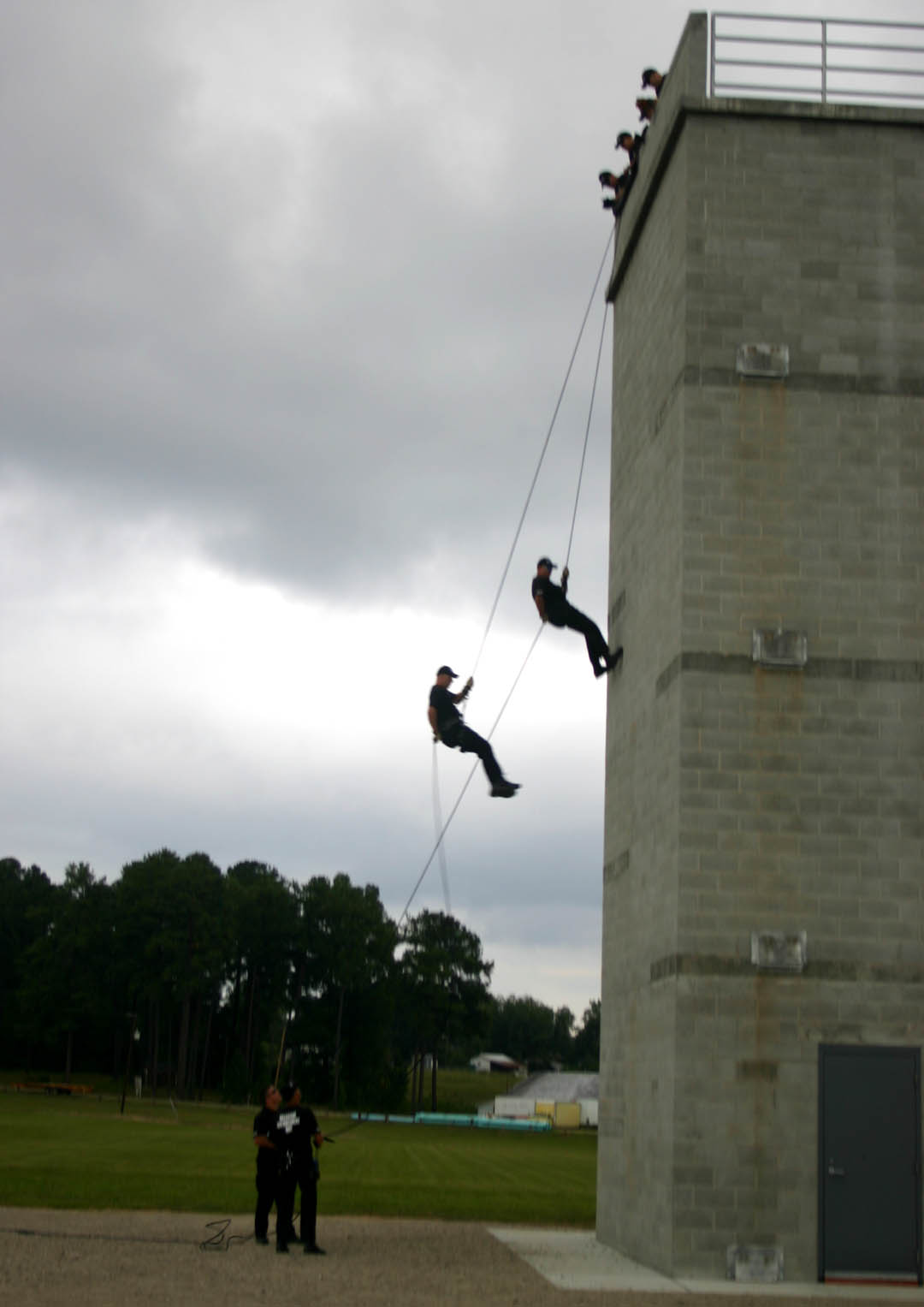 Click to enlarge,  Officers Brad Kidd and Doug Womack, of the Sanford Police Department rappel down the rescue tower at Central Carolina Community College's Emergency Services Training Center in Sanford during the Center's Open House Sept. 10. The 116-acre Center showed off its high-quality training facilities with the help of demonstrators from local police and fire departments. The belayers on the ground, holding the ropes, are Captain Wade Genthe and Officer Lee Allen.