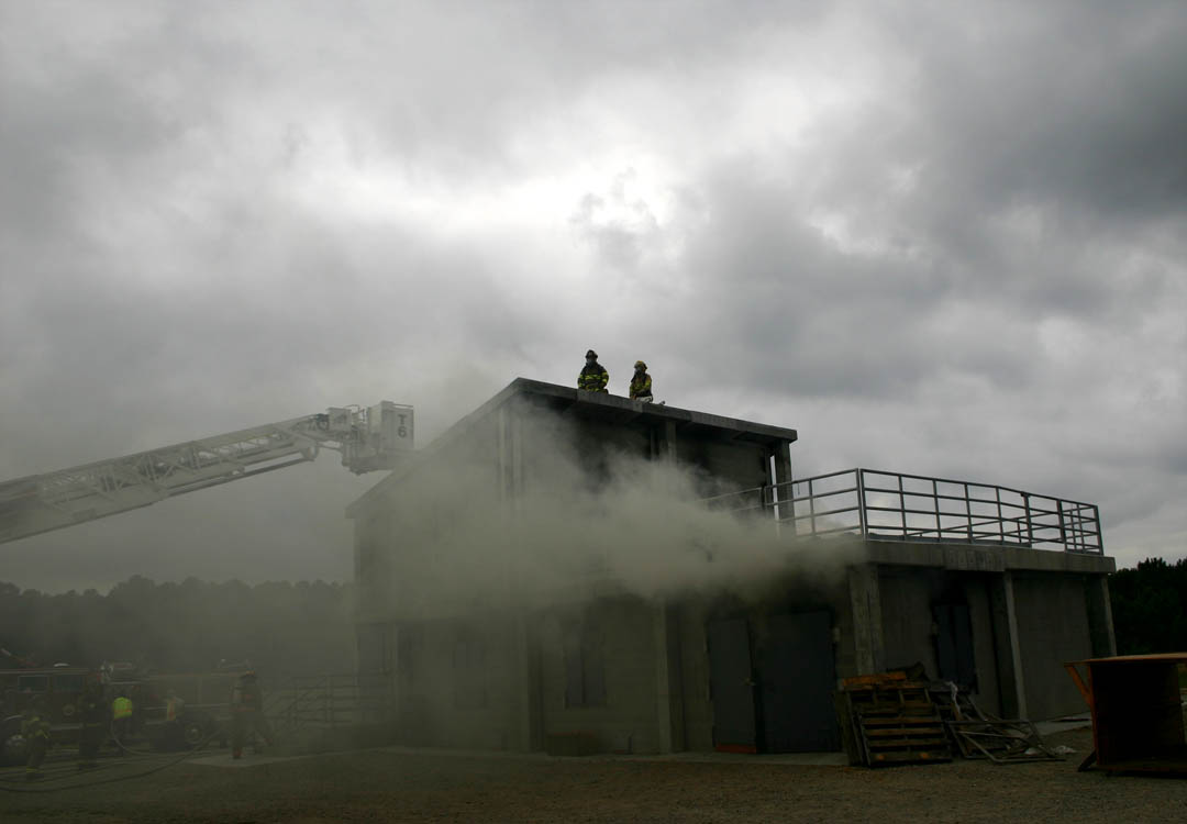 Click to enlarge,  Captain Brian Pilkington and firefighter Drew Womble of the Northview Fire Department prepare to cut a hole in the roof of the burn building at Central Carolina Community College's Emergency Services Training Center in Sanford. The hole will vent the heavy smoke surrounding firefighters working inside the building. The fire fighting demonstration was part of the ESTC's Open House Sept. 10 to show off the top-quality training facilities at the 116-acre facility. Local police and fire departments put on a variety of demonstrations.
