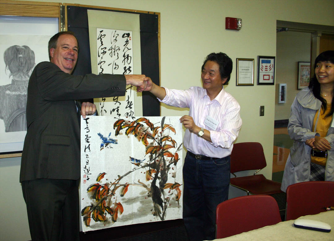Click to enlarge,  Chinese artist Yue-zi Lu (center) created a painting as a gift for Central Carolina Community College during the Chinese Art Exhibition hosted by the college Thursday. He presented it to CCCC President Bud Marchant (left) at the exhibition as Guanglin Dai (right), program manager for North Carolina State University's Confucius Institute, looks on. Lu and four other faculty of the College of Fine Arts at Nanjing Normal University in the People's Republic of China, showed their traditional Chinese painting and calligraphy during the exhibition at the McSwain Center in Sanford. The event was made possible by the partnership between CCCC's Confucius Classroom and NCSU's Confucius Institute, a center for the teaching of Mandarin Chinese and the sharing of Chinese culture.