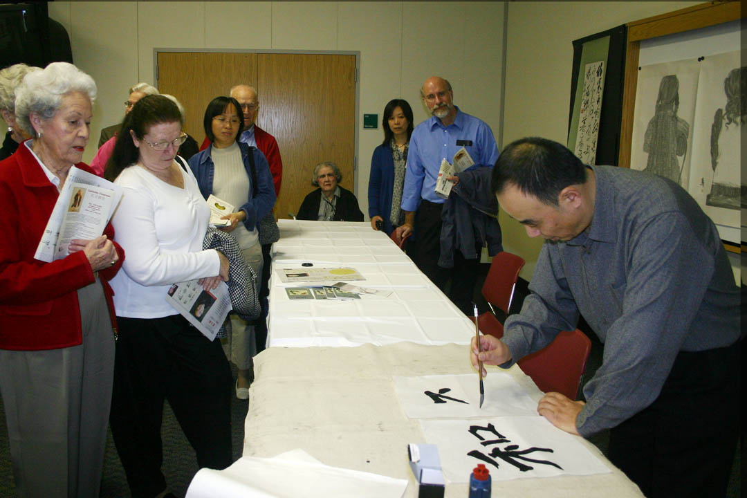 Click to enlarge,  Chinese calligraphic artist Ji-an Wang creates the word 'peace' in Chinese characters at the request of a visitor to the Chinese Art Exhibition hosted by Central Carolina Community College Thursday. Wang and four other faculty of the College of Fine Arts at Nanjing Normal University in the People's Republic of China, showed and demonstrated  their traditional Chinese painting and calligraphy during the exhibition at the McSwain Center in Sanford. The event was made possible by the partnership between CCCC's Confucius Classroom and North Carolina State University's Confucius Institute, a center for the teaching of Mandarin Chinese and the sharing of Chinese culture.