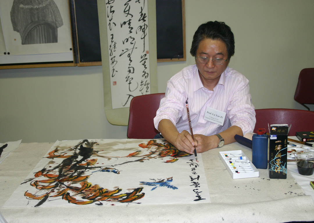 Click to enlarge,  Chinese artist Yue-zi Lu creates a painting of autumn leaves and birds as a gift for Central Carolina Community College during the Chinese Art Exhibition hosted  by the college Thursday. Lu and four other faculty of the College of Fine Arts at Nanjing Normal University in the People's Republic of China, showed and demonstrated their traditional Chinese painting and calligraphy during the exhibition at the McSwain Center in Sanford. The event was made possible by the partnership between CCCC's Confucius Classroom and North Carolina State University's Confucius Institute, a center for the teaching of Mandarin Chinese and the sharing of Chinese culture.