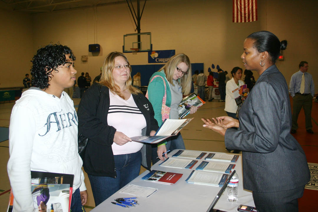 Click to enlarge,  Admissions counselors and representatives from almost 20 senior educational institutions visited Central Carolina Community College's Lee County Campus Nov. 19 for its University Transfer Day. They shared what their institutions have to offer students who complete their associate degree or university transfer programs at CCCC. Sanford residents (from left) Luis Mercado, a Lee Early College student, Donna Flowers, a CCCC Accounting and Business Administration student, and Rachael Krieger, also an LEC student, asked questions about what the institutions could offer them. Carlena Mills (right), a DeVry University admissions counselor, told them of the opportunities at her school. Lee Early College, located on CCCC's Lee County Campus, is a partnership between Lee County Schools and the college that enrolls high school students. The students graduate in five years with both a high school diploma and an associate degree at no cost. CCCC offers the first two years of a four-year college education close to home and for a fraction of the cost of a four-year institution. These institutions come to talk to CCCC students because of the quality education Central Carolina Community College provides. For more information, visit its web site,  www.cccc.edu .