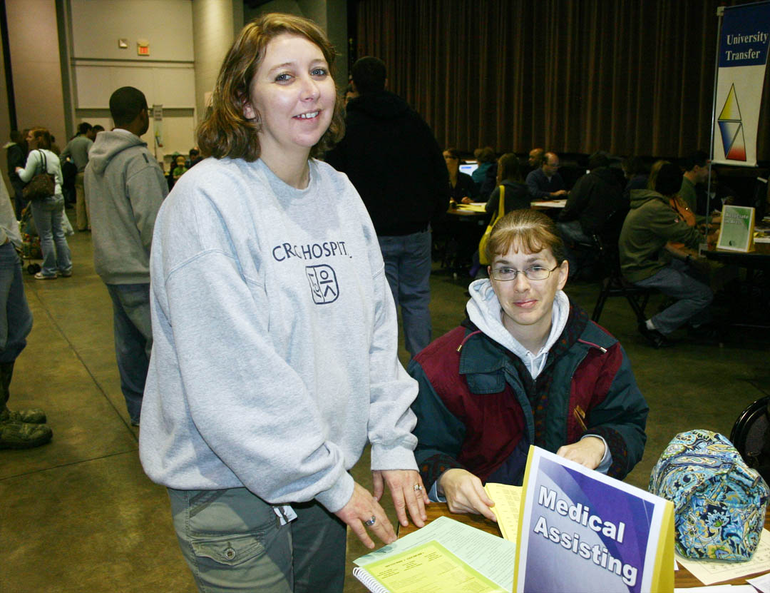 Click to enlarge,  Central Carolina Community College students Angela Ellis (standing), of Siler City, and Lisa Thomas, of Sanford, look over class listings as they wait their turn to enroll in medical assisting programs during the college's spring open registration Jan. 5 at the Dennis A. Wicker Civic Center, in Sanford. Open registration also took place at the campuses in Pittsboro and Lillington. Classes start Jan. 7. Late registration will continue through Jan. 13 at the Student Services offices at the Chatham, Harnett and Lee campuses. For more information about programs or registration, visit the college's web site, www.cccc.edu, or call one of the campuses: Pittsboro, (919) 542-6495; Lillington,