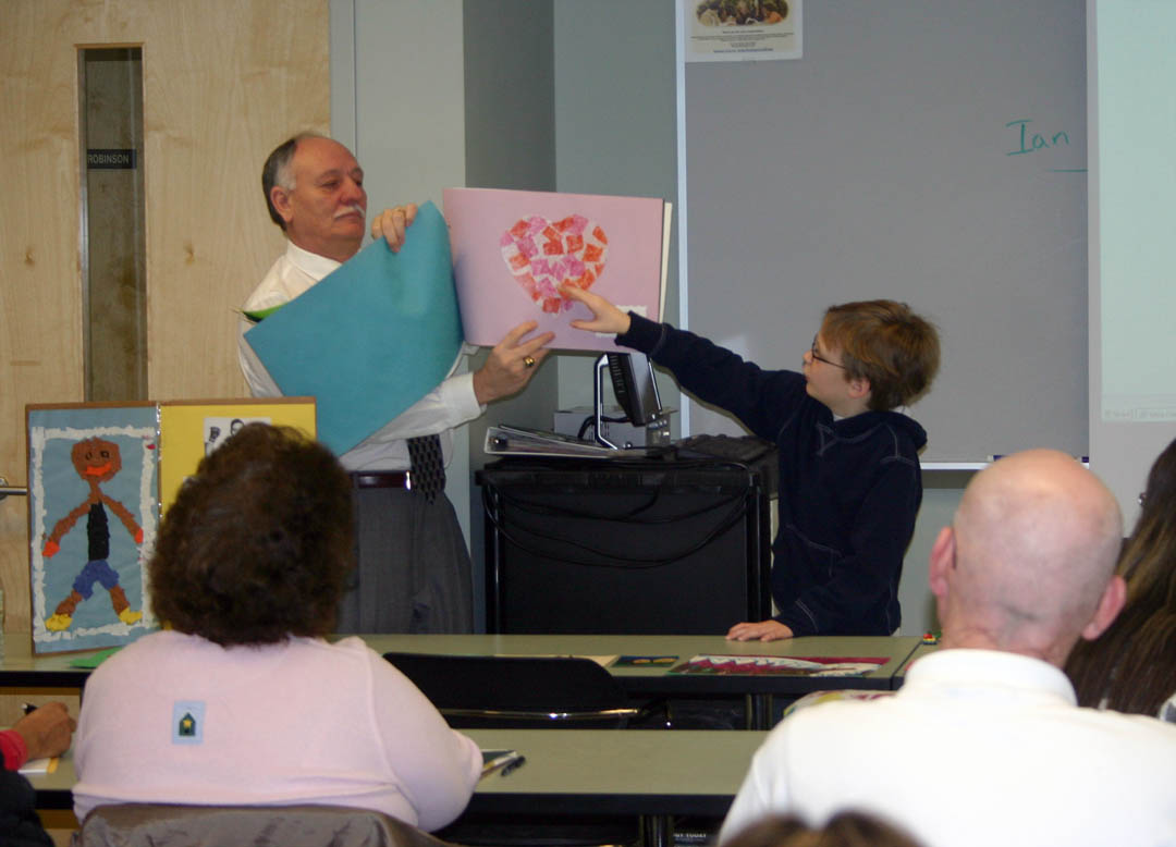 Click to enlarge,     Ten-year-old Ian Higgins (right) shares examples of his artwork with students in Central Carolina Community College's Early Childhood Education Creative Activities class Feb. 9 at the college's Lee County Campus. Higgins, a fourth grader at Mary Scroggs Elementary School, in Chapel Hill, is the grandson of class instructor David Leperi (left), of Pittsboro. The CCCC students are learning about the use of creative activities in educating young children. They were interested in getting a child's perspective on creative activities and ideas on what can be done from his work in clay modeling, watercolor, collage, and pastels. For more information about CCCC's Early Childhood Education programs, visit   www.cccc.edu/curriculum/majors/earlychildhood .