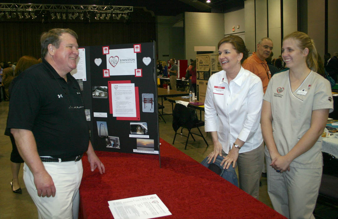 Click to enlarge,  Dr. Paul Porterfield (left), Chair of Central Carolina Community College's Veterinary Medical Technology program, stops to chat with a former student, Virginia Patterson (right), a 2001 program graduate who now works for Johnston Animal Hospital.  Patterson and Valerie Hill, the practice's office manager, were at the college's March 10 Career Fair at the Dennis A. Wicker Civic Center to recruit other Vet Tech students as employees for the practice. The Career Fair attracted representatives from about 55 businesses, private and government agencies, and military recruiters to speak with the several hundred students in attendance about career opportunities with them.