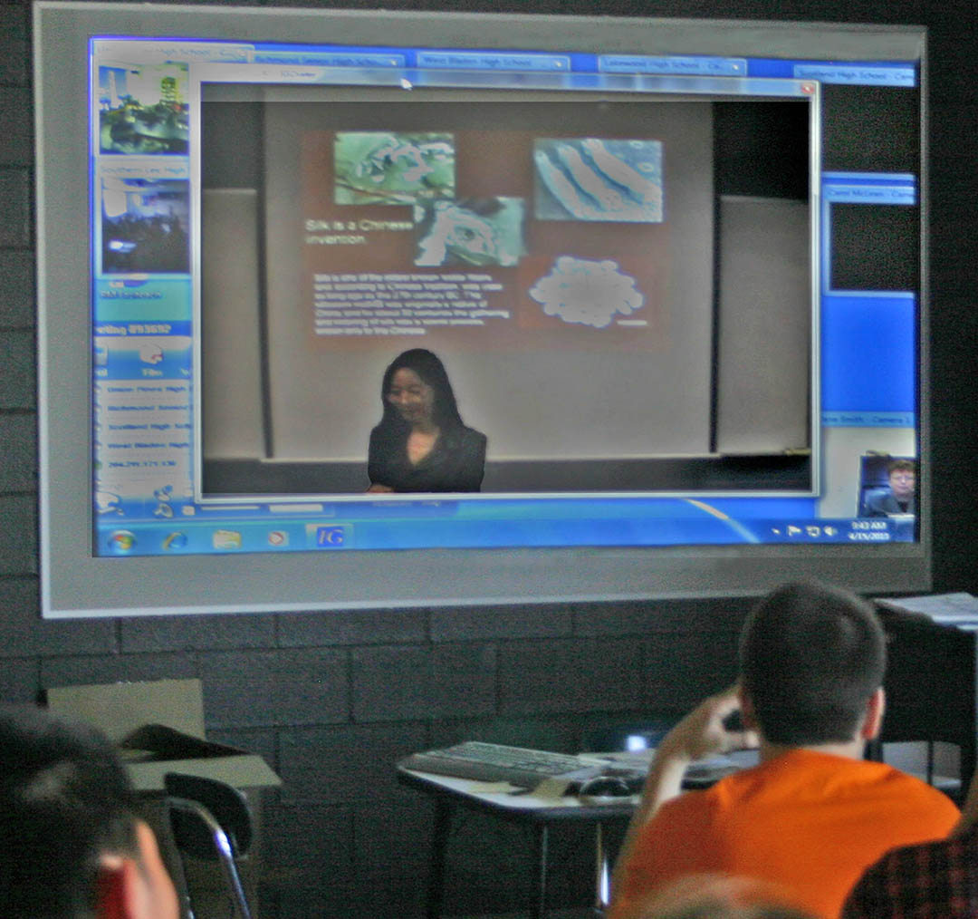 Click to enlarge,  Professor Shuya Che (on-screen, center), instructor at Central Carolina Community College's Confucius Classroom, delivers a presentation on Chinese culture and language via videoconferencing to about 30 Southern Lee High School students as well as students located at five other high schools in central North Carolina. Students at each of the schools were able to see and hear both Che and the other students participating in the April 15 videoconference. The videoconference was made possible by the BRAC Regional Task Force's Distributed Learning Network. The network, with its hub at the All American Center for Workforce Innovation at Fayetteville Technical Community College, was established by the RTF as a tool to expand educational opportunities to prepare a workforce for the competitive global economy.