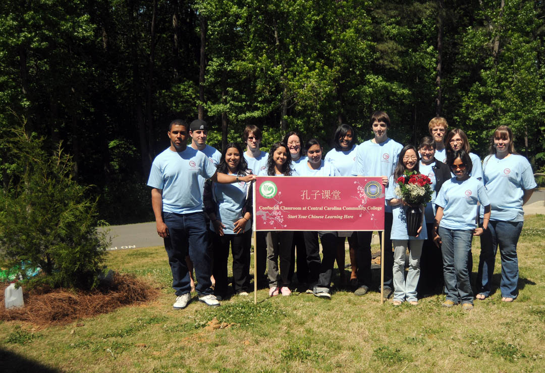 Click to enlarge,  Professor Shuya Che (front, second from right), Central Carolina Community College Confucius Classroom instructor, and members of her Elementary Chinese-1 class planted an Eastern Redcedar tree (left) April 29 on the college's Lee County Campus. The tree planting commemorated Chinese Arbor Day-March 12, U.S. National Arbor Day-April 30; and Chinese Labor Day-May 1. In addition to the tree planting, Che spoke about the origins and meaning of Chinese Arbor Day. The class also celebrated the birthdays of class members whose birthdays fall between July and December. Following the tree planting, the students presented Che with a vase of flowers in appreciation for her enthusiasm in teaching. Elementary Chinese-1 students taking part in the tree planting were  (front from left) Malcolm Murchison, Che, and Jemima Boncales; (second row, from left) Aleida Domingoes, Denise Garcia, Paola Fernandez, David Gietzen, Spanish instructor Janet Zurbach, Roseanna Terry and Michelle Womble; and, (back row, from left) Nicholas Kehagias, Daniel Buchanan, Rebecca Francis, Juanita Smith, and Tony Diaz. For more information on Central Carolina Community College's Confucius Classroom, go online to  www.cccc.edu/confucius .