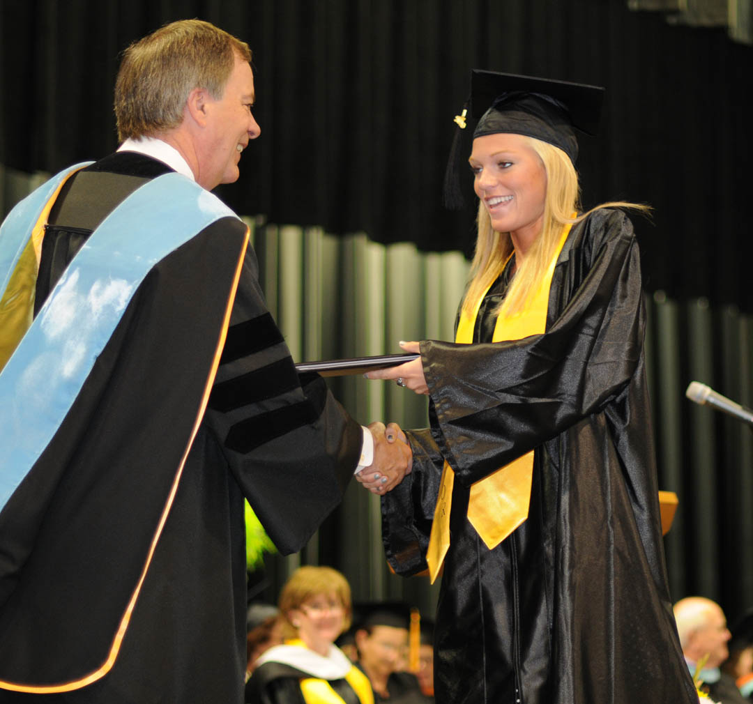 Click to enlarge,  Jamie Yeatman (right), of Harnett County, receives her Associate in Applied Science in Laser and Photonics Technology from Central Carolina Community College President Bud Marchant during the college's May 13 Spring Commencement at the Dennis A. Wicker Civic Center.