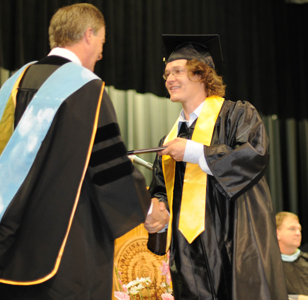 Click to enlarge,  Jeremy Rushlow (right), of Chatham County, receives his Associate in Applied Science in Alternative Energy Technology: Biofuels degree from Central Carolina Community College President Bud Marchant during the college's May 13 Spring Commencement at the Dennis A. Wicker Civic Center.