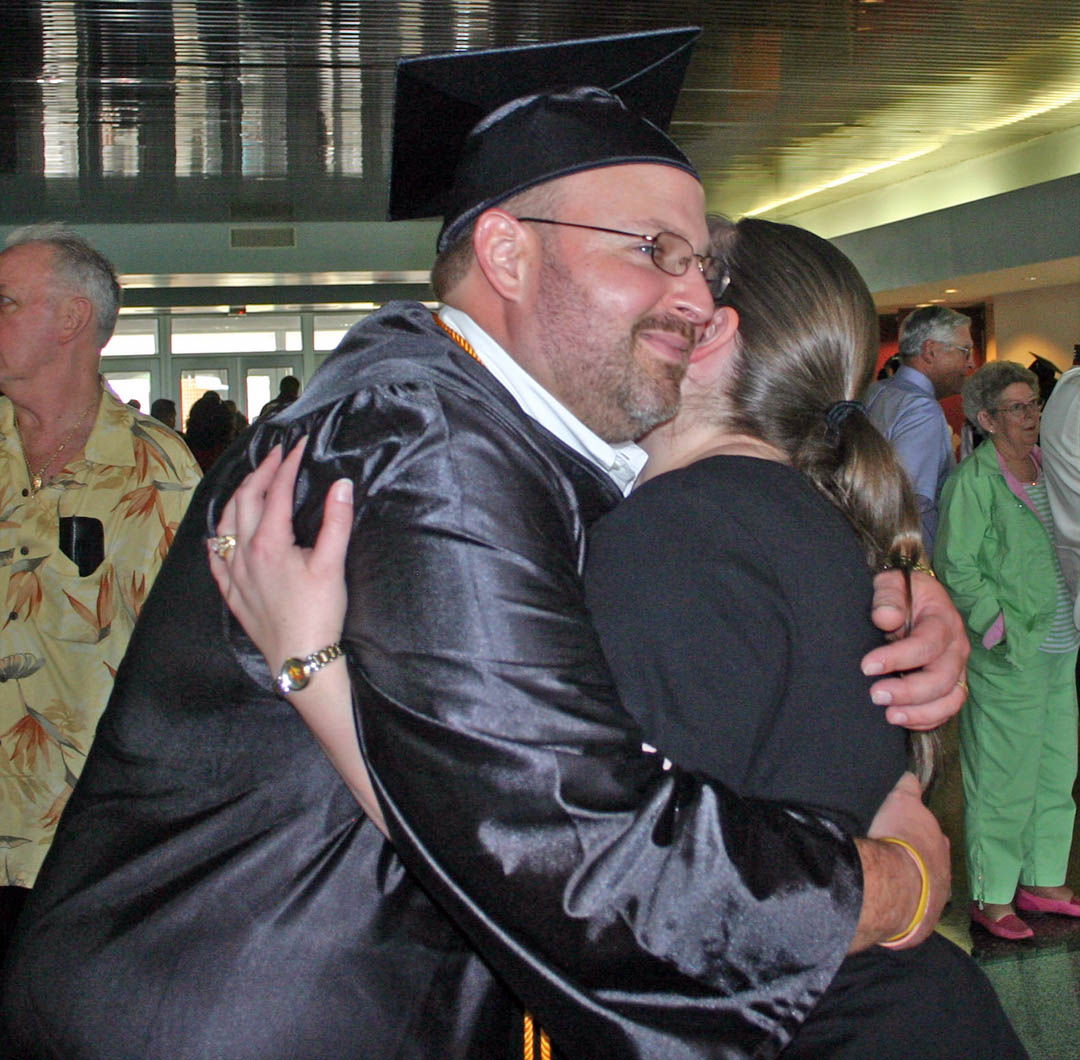 Click to enlarge,  Richard Bogart, of Chatham County, gets a big hug from his wife, Kristina, following the Central Carolina Community College May 13 Spring Commencement at the Dennis A. Wicker Civic Center. Bogart had worked in injection molding for more than 17 years before being laid off due to the recession. He came to CCCC and earned his Associate in Applied Science in Electronics Engineering Technology and is now looking forward to a new career.