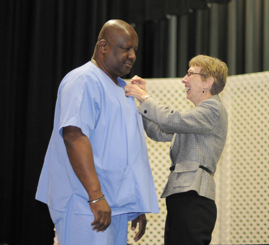 Click to enlarge,  Rodney Butler (left), of Lee County, receives his Nursing Assistant I pin from Judy Farmer, Lee County Continuing Education health program coordinator, during Central Carolina Community College's Continuing Education Medical Programs graduation May 27 in the Dennis A. Wicker Civic Center. About 190 students completed certificates during the spring semester in the areas of EKG Technician, Advanced EKG, EKG Monitor Technician, Optometric Assistant, Pharmacy Technician, Phlebotomy Technician, Nursing Assistant Refresher, Nursing Assistant I or II, Drug Collection Specialist, or Medical Terminology. About 40 did their training under the auspices of the college's JobsNOW program, which trains unemployed workers in new careers within a few months.
