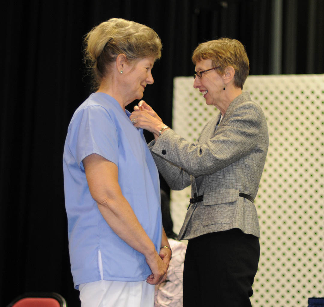 Click to enlarge,  Mary Cotton (left), of Chatham County, receives her Nursing Assistant I pin from Judy Farmer, Lee County Continuing Education health program coordinator, during Central Carolina Community College's Continuing Education Medical Programs graduation May 27 in the Dennis A. Wicker Civic Center. About 190 students completed certificates during the spring semester in the areas of EKG Technician, Advanced EKG, EKG Monitor Technician, Optometric Assistant, Pharmacy Technician, Phlebotomy Technician, Nursing Assistant Refresher, Nursing Assistant I or II, Drug Collection Specialist, or Medical Terminology. About 40 did their training under the auspices of the college's JobsNOW program, which trains unemployed workers in new careers within a few months.