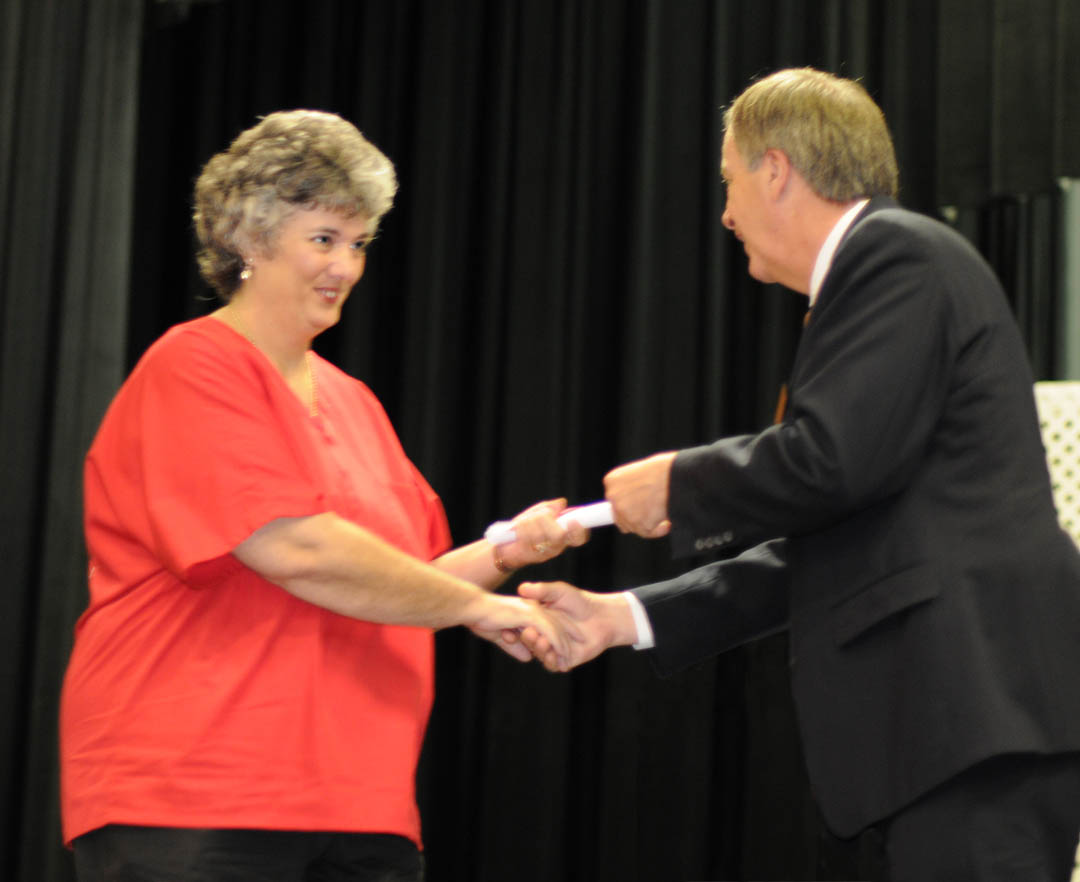Click to enlarge,  Susan Bryant (left), of Lee County, receives her Phlebotomy Certificate from Central Carolina Community College President Bud Marchant, during the college's Continuing Education Medical Programs graduation May 27 in the Dennis A. Wicker Civic Center. About 190 students completed certificates during the spring semester in the areas of EKG Technician, Advanced EKG, EKG Monitor Technician, Optometric Assistant, Pharmacy Technician, Phlebotomy Technician, Nursing Assistant Refresher, Nursing Assistant I or II, Drug Collection Specialist, or Medical Terminology. About 40, including Bryant, did their training under the auspices of the college's JobsNOW program, which trains unemployed workers in new careers within a few months. Bryant returned to school after being laid off by Moen and earned both her Phlebotomy and Drug Collection Specialist certificates.