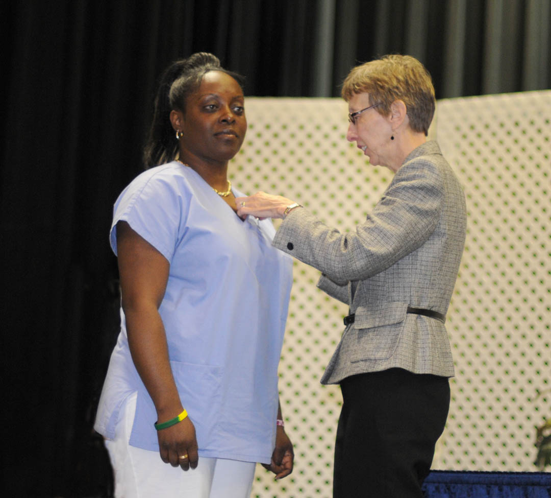 Click to enlarge,  Nichole Henry (left), of Chatham County, receives her Nursing Assistant I pin from Judy Farmer, Lee County Continuing Education health program coordinator, during Central Carolina Community College's Continuing Education Medical Programs graduation May 27 in the Dennis A. Wicker Civic Center. About 190 students completed certificates during the spring semester in the areas of EKG Technician, Advanced EKG, EKG Monitor Technician, Optometric Assistant, Pharmacy Technician, Phlebotomy Technician, Nursing Assistant Refresher, Nursing Assistant I or II, Drug Collection Specialist, or Medical Terminology. About 40 did their training under the auspices of the college's JobsNOW program, which trains unemployed workers in new careers within a few months.