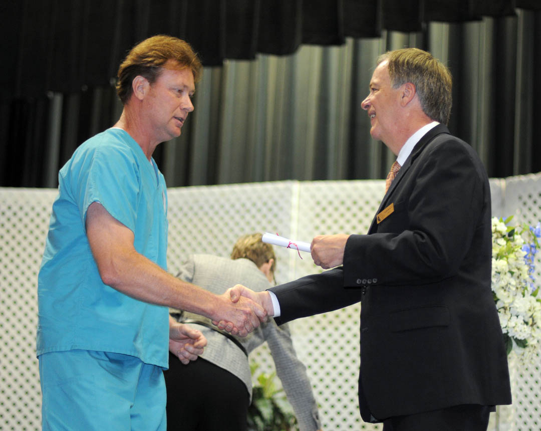 Click to enlarge,  Jackson Parrish Jr. (left), of Harnett County, receives his Nursing Assistant II Certificate from Central Carolina Community College President Bud Marchant during the college's Continuing Education Medical Programs graduation May 27 in the Dennis A. Wicker Civic Center. About 190 students completed certificates during the spring semester in the areas of EKG Technician, Advanced EKG, EKG Monitor Technician, Optometric Assistant, Pharmacy Technician, Phlebotomy Technician, Nursing Assistant Refresher, Nursing Assistant I or II, Drug Collection Specialist, or Medical Terminology. About 40 did their training under the auspices of the college's JobsNOW program, which trains unemployed workers in new careers within a few months.