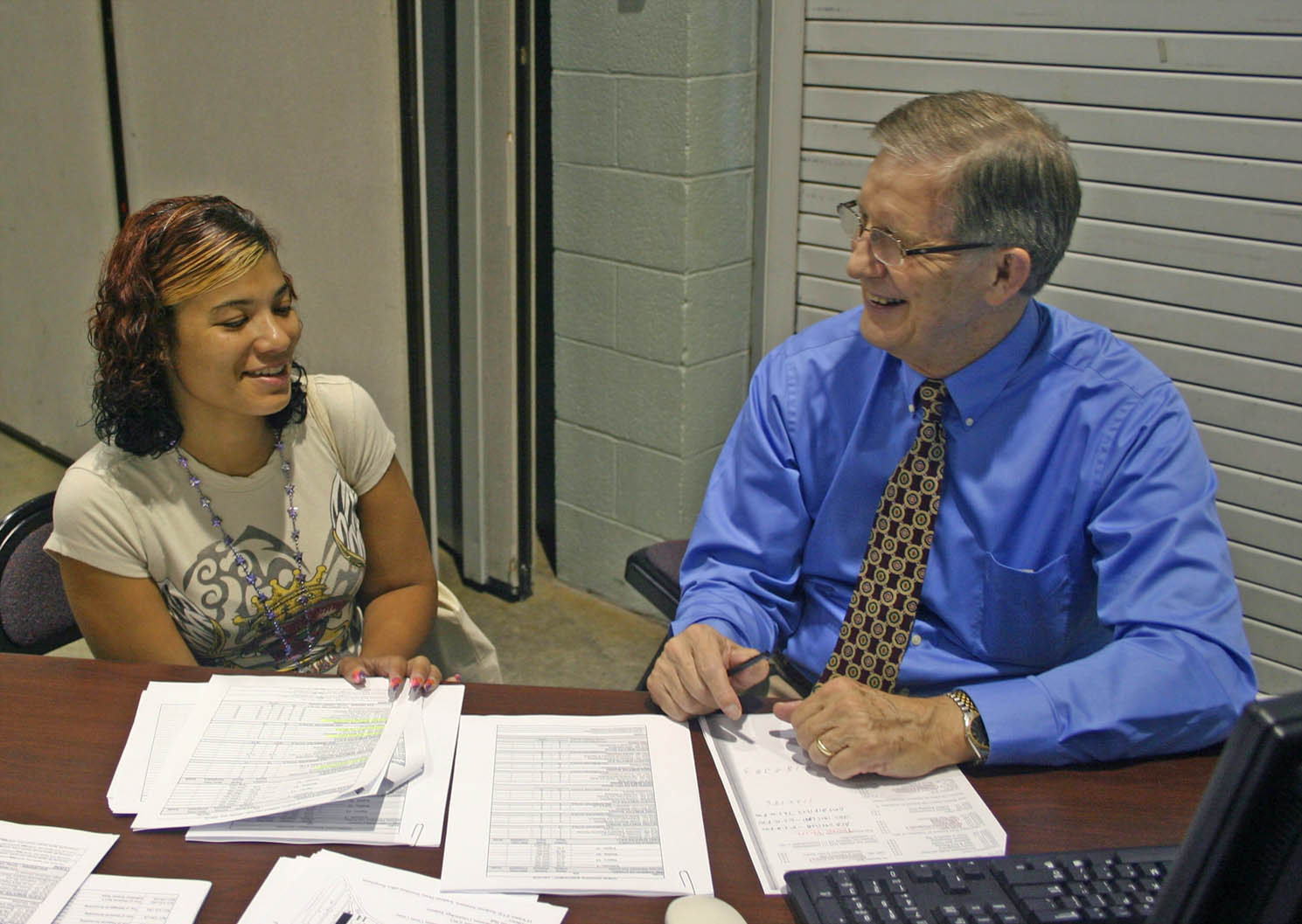 Click to enlarge,  Sharonda Woods (left), of Sanford, discusses her Business Administration class schedule with George Clayton, Central Carolina Community College lead instructor for Business Technologies, during the college's fall semester Open Registration Tuesday, Aug. 17, at the Dennis A. Wicker Civic Center. Fall classes begin Monday, Aug. 23. Late registration extends through 3 p.m. Friday, Aug. 27, at the college's campuses in Chatham, Harnett and Lee counties. For more information on registering or classes, visit the college's Web site,  www.cccc.edu .