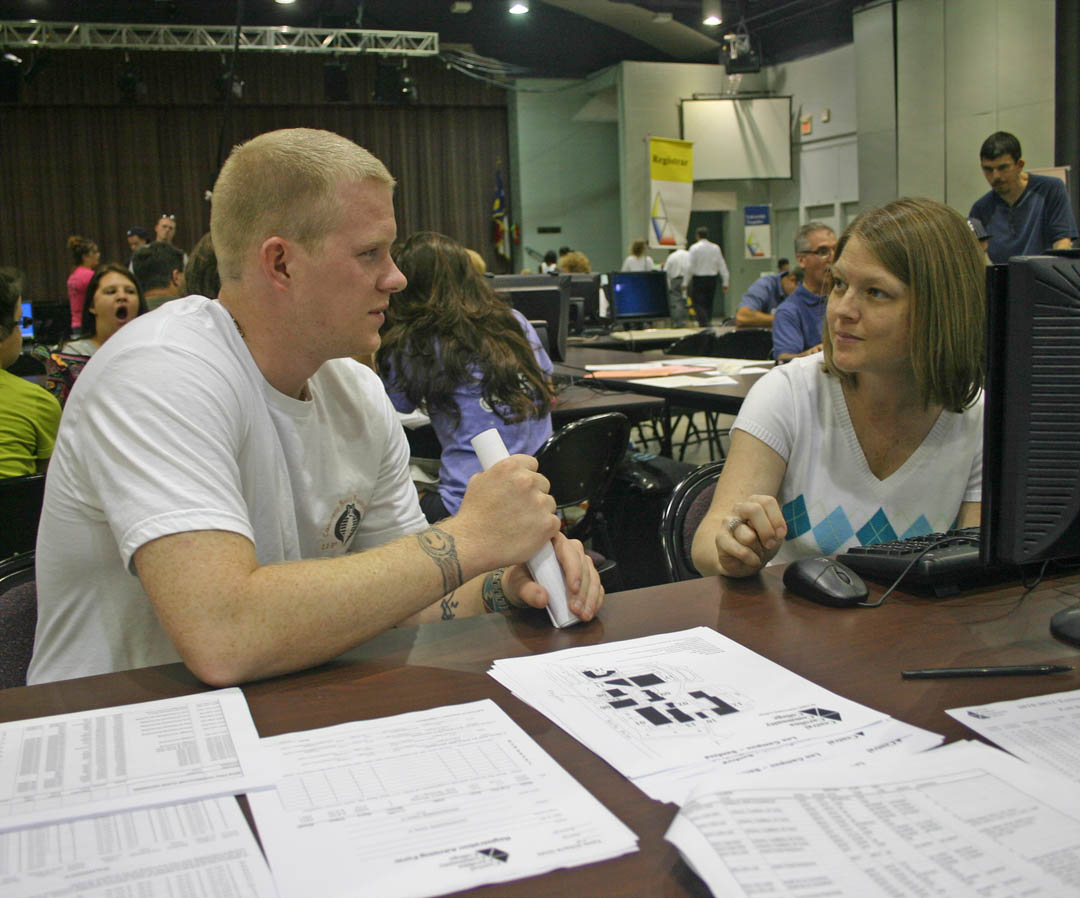Click to enlarge,  David Mundy (left), of Cameron, Harnett County, discusses his class schedule with Central Carolina Community College admissions counselor Jamee Stiffler during fall semester Open Registration Tuesday, Aug. 17, at the Dennis A. Wicker Civic Center. Mundy is a first-year University Transfer student. Fall classes begin Monday, Aug. 23. Late registration extends through 3 p.m. Friday, Aug. 27, at the college's campuses in Chatham, Harnett and Lee counties. For more information on registering or classes, visit the college's Web site,  www.cccc.edu .