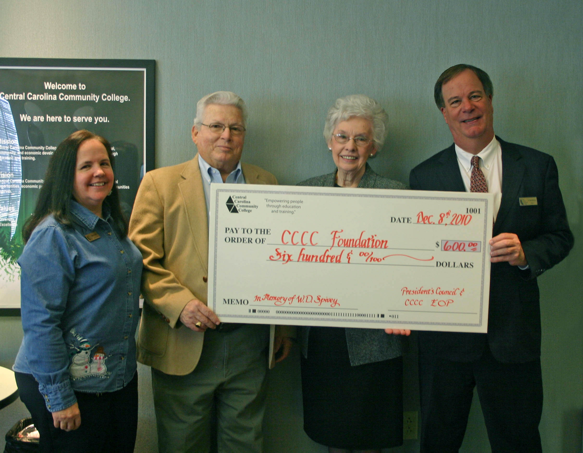 Click to enlarge,  Linda Spivey (second from right), employment specialist in the Human Resources Department at Central Carolina Community College, retired in December after a 33-year career with the college. In her honor, the CCCC President's Council and the college's chapter of the North Carolina Association of Educational Office Professionals established the Walter D. Spivey Memorial Scholarship with the CCCC Foundation. Walter, the son of Linda and David Spivey, graduated from the college. He was the owner and operator of Mid-Carolina Electric Co., in Sanford, when he passed away in 2010. Martha Wilkie (left), NCAEOP District 7 president, and CCCC President Bud Marchant (right), present the check to the Spiveys. Linda served under four of the college's five presidents and helped found the CCCC EOP in 1983. She has been an officer in the organization at the college, regional and state level, including state president in 2009-10. She was honored as the local and District 7 Educational Office Professional of the Year in 1992-93 and 2004-05. She was also honored as the District 7 EOPY for 2010-11 and received the organization's President's Award. Linda is a graduate of Sanford Business College and CCCC.