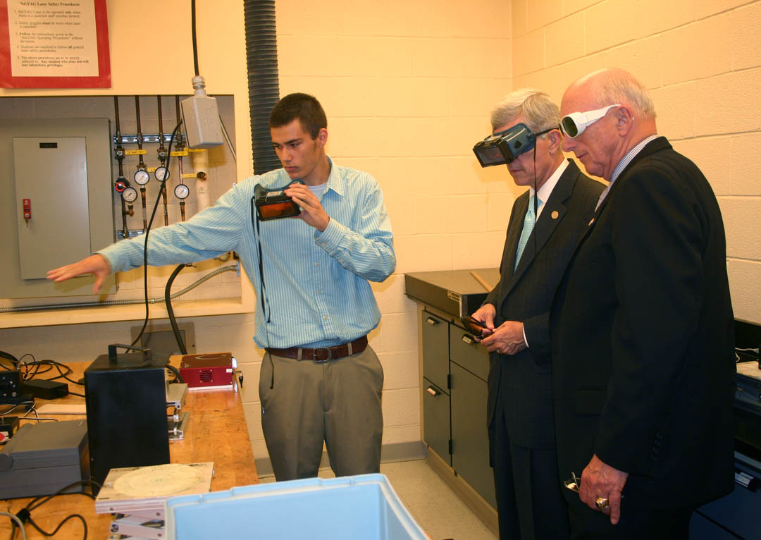 Click to enlarge,  Central Carolina Community College laser and photonics student John-Kevin Frazee, of Dunn, describes the equipment in the college's Nd:YAG solid state laser laboratory before giving a demonstration to North Carolina Lt. Gov. Walter Dalton (center) and Dunn Mayor Oscar Harris (right). Dalton visited the college's Harnett County Campus April 28 to speak on the future of community colleges and tour the campus' laser and photonics laboratories. Harris was among those on the tour.