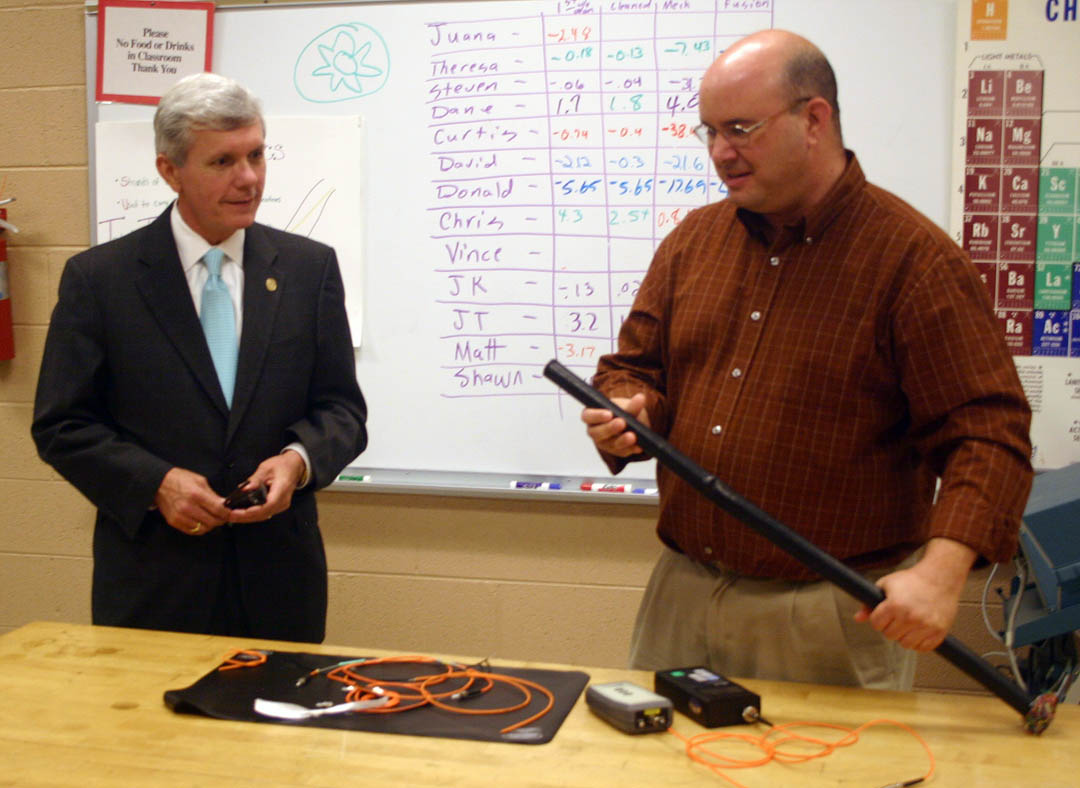 Click to enlarge,  North Carolina Lt. Gov. Walter Dalton (left) visited Central Carolina Community College's Harnett County Campus April 28 to speak on the future of community colleges and tour the campus' laser and photonics laboratories. Laser and photonics student David Oliver (right), of Lillington, compares the bandwidth capabilities versus size of the fiber optic cable on the table to the standard, multi-wire copper cable he is holding.