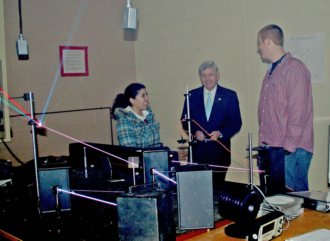 Click to enlarge,  Central Carolina Community College laser and photonics technology students Juana Bethancourth (left), of Sanford, and Shawn Palmer (right) of Fuquay, demonstrate an argon krypton laser for North Carolina Lt. Gov. Walter Dalton during his April 28 visit to the college's Harnett County Campus, in Lillington. Dalton spoke to an audience of about 100 on the future of community colleges and then toured the campus' laser and photonics laboratories.