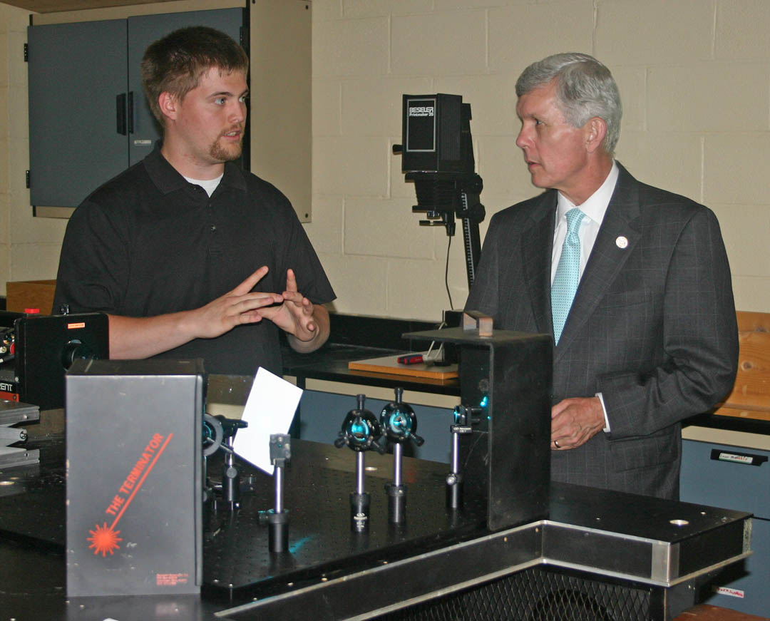 Click to enlarge,  North Carolina Lt. Gov. Walter Dalton (right) visited Central Carolina Community College's Harnett County Campus April 28 to speak on the future of community colleges and tour the campus' laser and photonics laboratories. Laser and photonics student Curtis Paul (left), of Lillington, explains the functioning of an interferometer, using an argon ion laser, to the lieutenant governor.