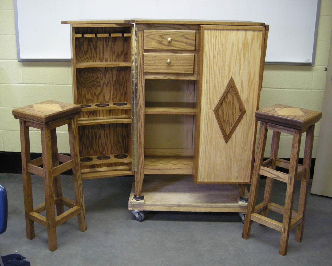 Click to enlarge,  This handsome wood cabinet, with two matching stools, is one of about 100 hand-crafted pieces of wood and metal work that will be auctioned off at the 11th annual Central Carolina Community College Foundation Furniture Auction Saturday, June 4, in the Multipurpose Room of the Miriello Building on the Harnett County Campus, 1075 E. Cornelius Harnett Blvd., Lillington. Viewing starts at 11 a.m. and bidding, at 12 p.m. Students in the college's carpentry and welding programs at the Harnett Correctional Institution created these well-built pieces, learning marketable skills to become contributing members of their communities upon release. Proceeds from the Auction fund a scholarship at the college.