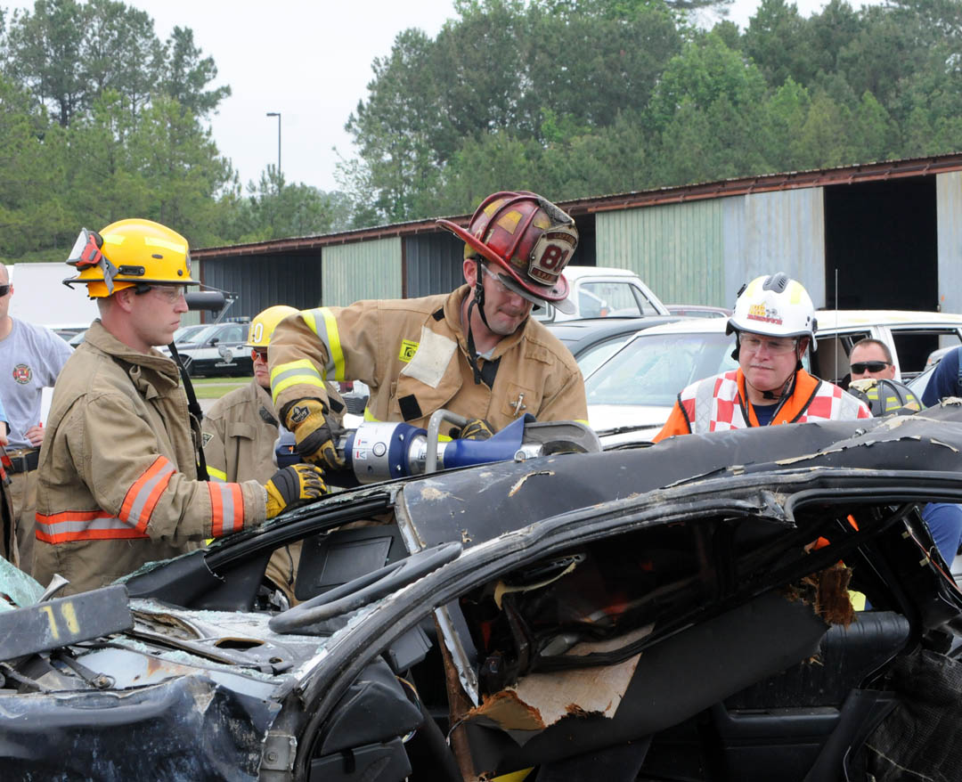 Click to enlarge,  Firefighter Scott Padgett, of Southern Pines Fire and Rescue, uses a hydraulic spreader to widen a cut around a crashed vehicle doorpost in order to remove the door during the Extrication College training May 13 at Central Carolina Community College's Emergency Services Training Center. Instructor Billy Leach Jr. (right) instructs Padgett on widening the pie-shaped cut while firefighter Timothy Smith (left), driver/operator for SPFD and a volunteer with the Deep River Volunteer Fire Department, stands ready to assist.  Cutting around a doorpost to remove a door can save critical time in reaching accident victims in crashed vehicles. For more information about the ESTC and its programs, call Director of Emergency Services Landis Phillips, (919) 777-7779, or email at  ljphillips@cccc.edu .