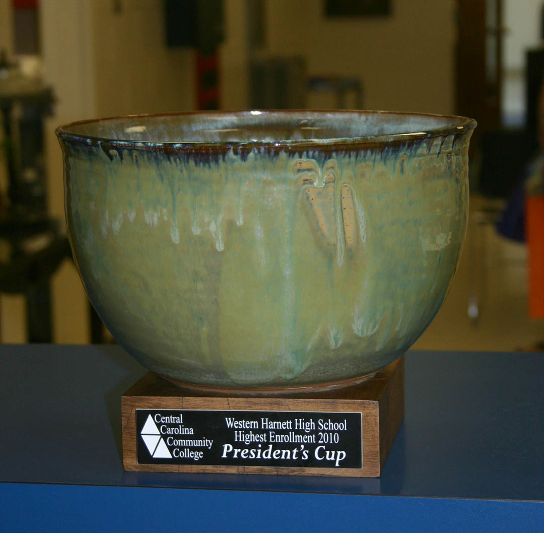 Click to enlarge,  Western Harnett High School is the first recipient of Central Carolina Community College's President's Cup, which will be presented annually to the high school having the highest percentage of graduates continuing their education at CCCC. Of Western Harnett's 242 graduates in 2010, 46 — 19 percent — enrolled at CCCC. Administrators from the college visited the high school June 13 to present the Cup. Joyce Bryan, CCCC ceramics instructor and a professional potter with her own business, Stone Crow Pottery, in Pittsboro, made the glazed ceramic bowl. For more information about programs at Central Carolina Community College, visit its Web site,  www.cccc.edu .
