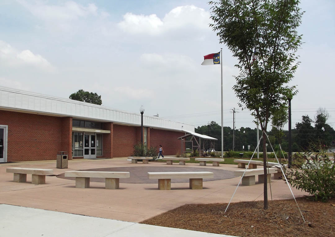 Click to enlarge,  Central Carolina Community College's Lee County Campus has a new, spacious look to its main entrance, the area between the Library and Bell Hall (pictured looking toward Kelly Drive). Over the past year, trees and vegetation were removed from the area, a new courtyard with sandstone benches installed, and new landscaping planted. The design is by United Biospheres, of Siler City. Visitors, employees and students now find the area a more inviting and functional part of the campus.